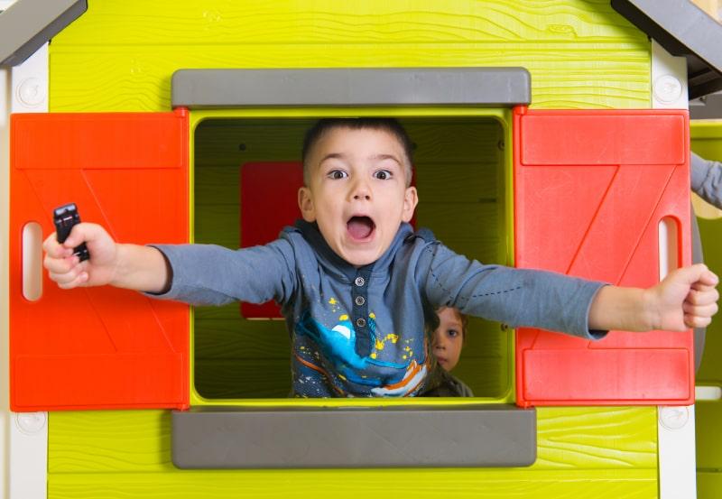 Kleiner-Junge-im-Spielzeughausfenster