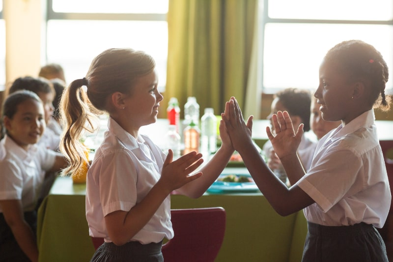 Lachelnde-Schulmadchen-die-ein-Klatschspiel-spielen