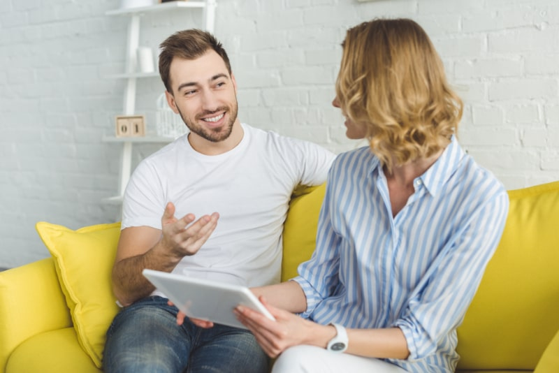 Lachelnder-Mann-im-Gesprach-mit-Freundin-mit-Tablet-in-der-Hand
