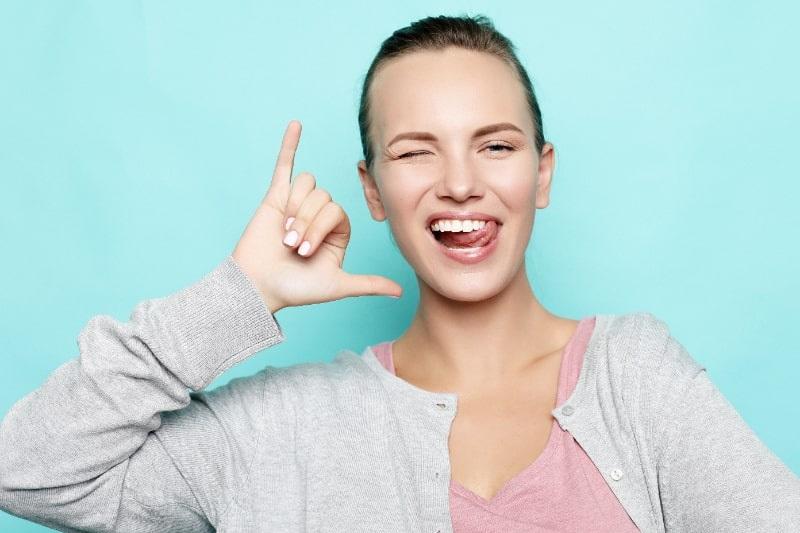 Lustiges-Madchen-das-ihre-Zunge-zeigt-wahrend-sie-vor-Studiohintergrund-posiert.-Emotionale-positive-junge-Frau-die-Gesichter-macht