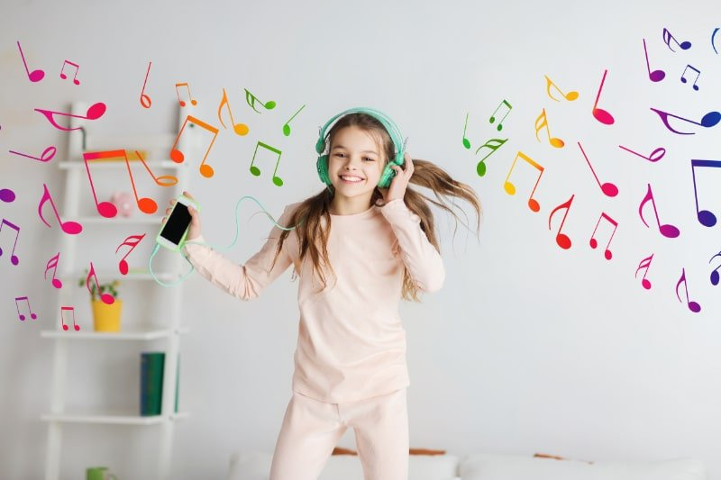 Madchen-springt-mit-Smartphone-und-Kopfhorern-aufs-Bett