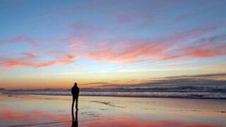 Mann, der schönen Sonnenuntergang am Strand betrachtet