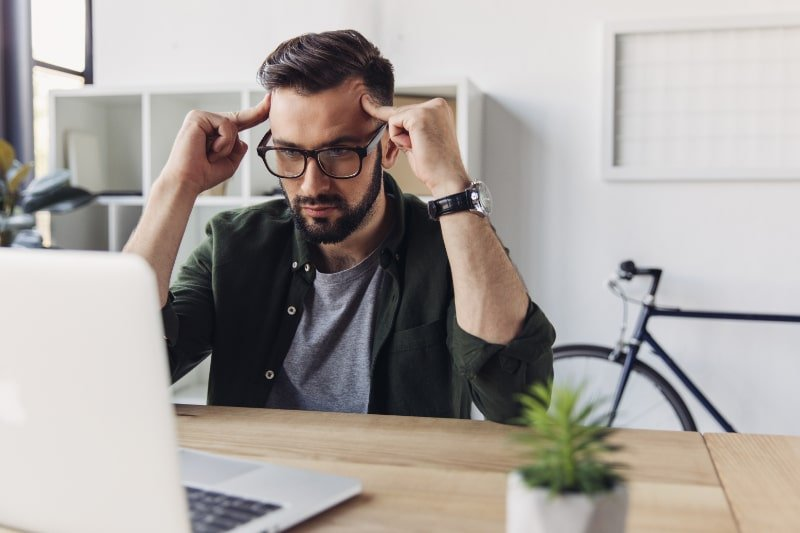 Mann-mit-Laptop-und-Denkt-nach