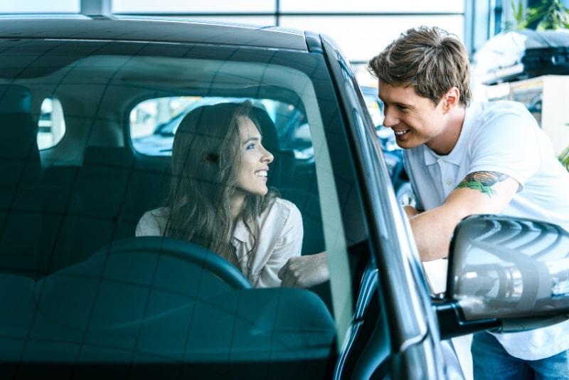 Mann-spricht-mit-Frau-die-im-Auto-sitzt