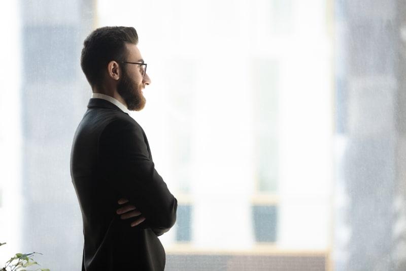 Mann-steht-am-Fenster-traumt-von-zukunftigen-Zielen-neue-Moglichkeiten