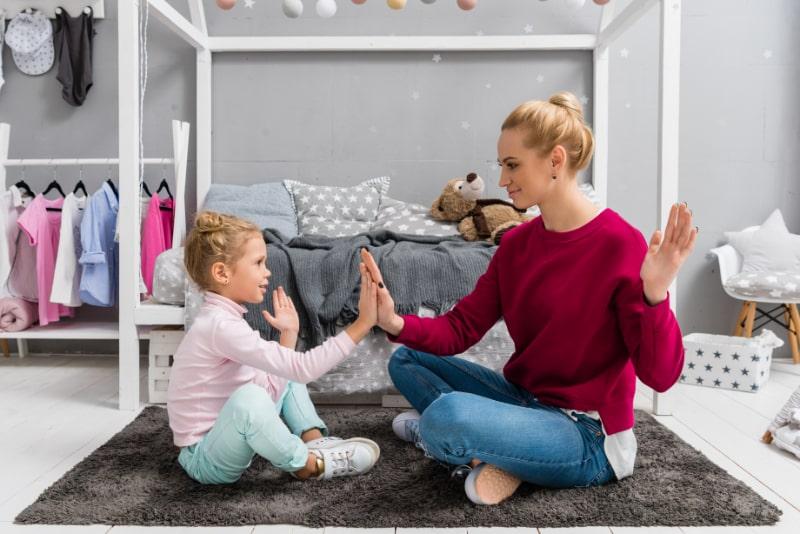 Mutter-und-Tochter-spielen-Pattycake-wahrend-sie-auf-dem-Boden-sitzen