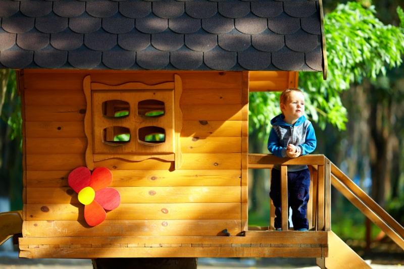 Nettes-Baby-das-im-Baumhaus-spielt-sonnig-im-Freien