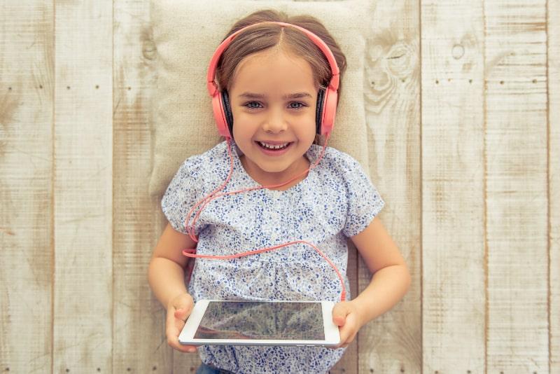 Nettes-kleines-Madchen-das-Musik-auf-einem-iPad-hort