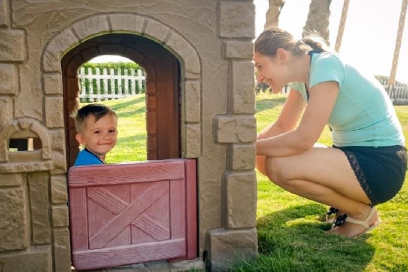Portrat-eines-glucklich-lachelnden-Kleinkindjungen-der-im-Spielzeugplastikhaus-auf-dem-Kinderspielplatz-im-Park-spielt