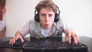 Porträt eines lustigen Spielers mit erstauntem Gesicht beim Spielen auf einem Computer.