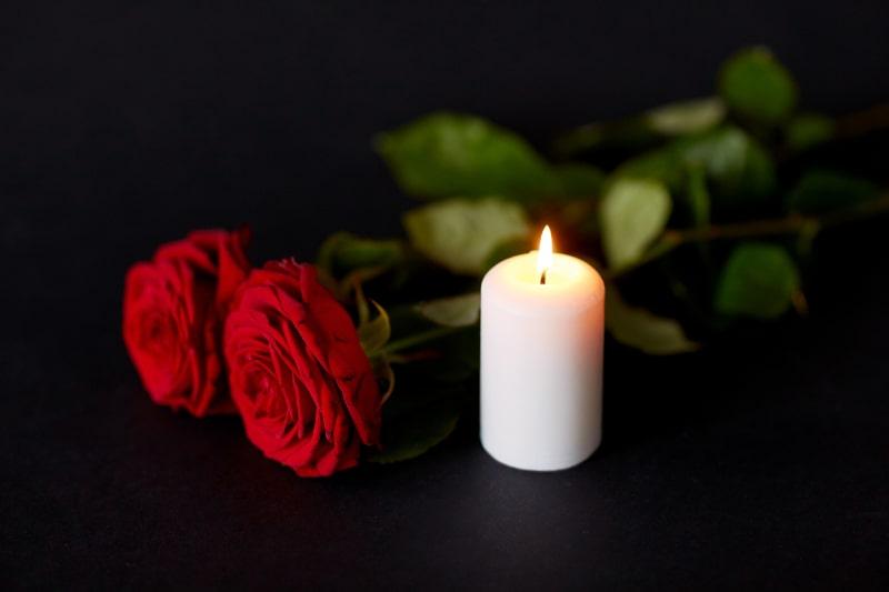 Rote-Rosen-und-brennende-Kerze-auf-schwarzem-Hintergrund