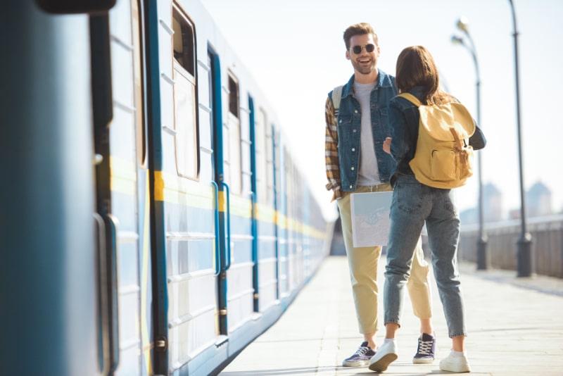 Ruckansicht-einer-stilvollen-Touristin-mit-Rucksack-die-mit-einem-lachelnden-Freund-in-Sonnenbrille-an-der-U-Bahn-Station-im-Freien-spricht-