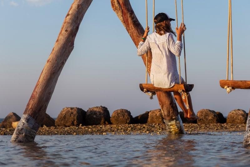 Ruckansicht-weiblich-sitzend-auf-der-Schaukel-am-Meeresufer