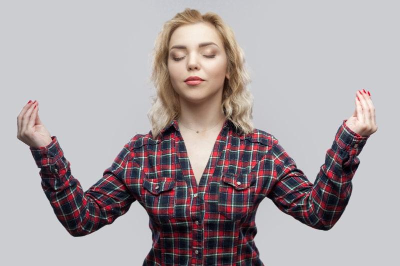 Ruhige-schone-blonde-junge-Frau-in-lassigem-rot-kariertem-Hemd-die-mit-erhobenen-Armen-und-geschlossenen-Augen-steht-wahrend-sie-auf-grauem-Hintergrund-meditiert.