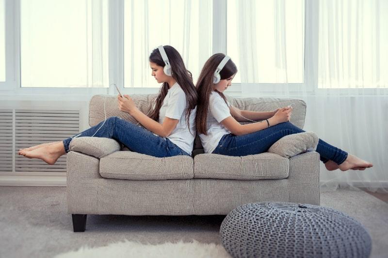 Schwestern-im-Teenageralter-mit-Smartphone-und-Kopfhorern-die-Musik-horen-und-in-sozialen-Netzwerken-kommunizieren
