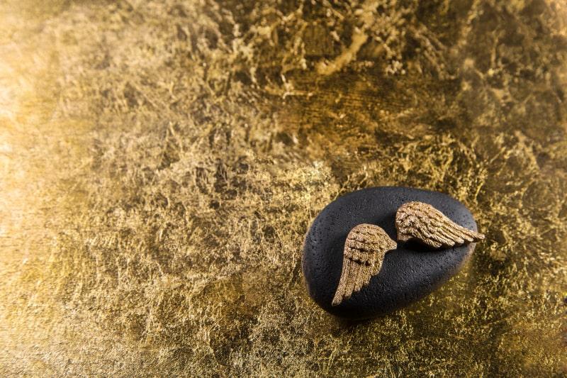 Stein-mit-goldenen-Flugeln-fur-einen-eleganten-Hintergrund