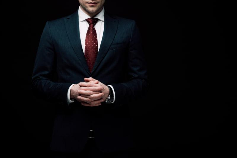 Teilansicht-eines-selbstbewussten-Geschaftsmannes-der-mit-geballten-Handen-isoliert-auf-schwarzem-menschlichem-Emotions-und-Ausdruckskonzept-steht