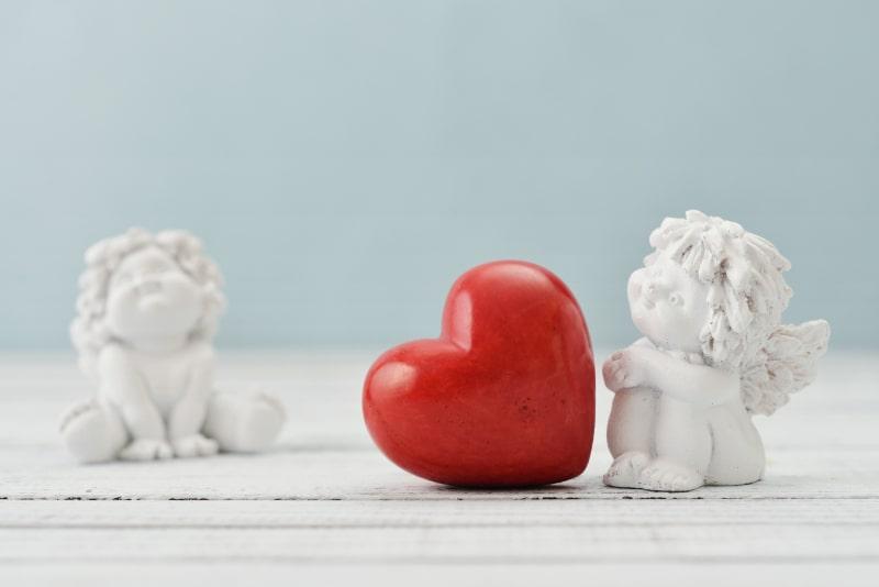 Valentinstag-Konzept-zwei-kleine-weise-Engelsstatuen-und-rotes-Herz