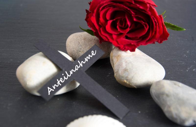 rote-Rose-Steine-schwarzes-Kreuz-mit-Uberschreibung