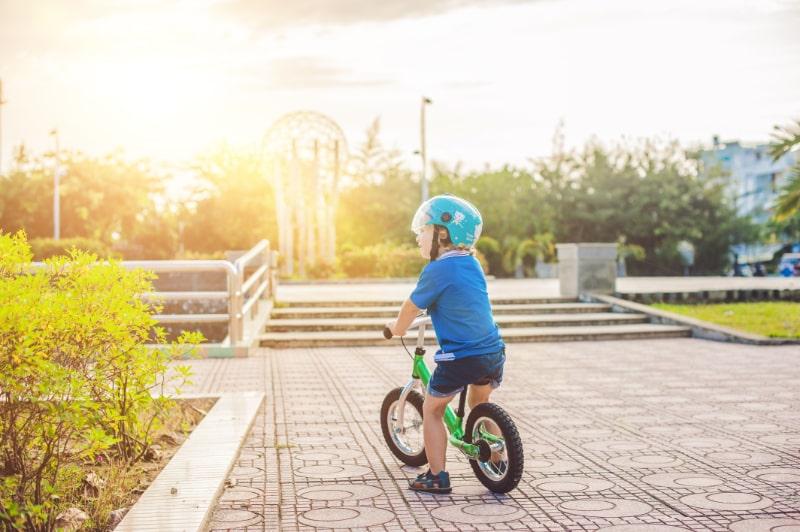 Blonder-Kinderjunge-der-unter-der-Sonne-Fahrrad-fahrt
