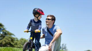 Familie im Park, Junge, der Laufrad fährt