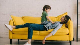 Kleiner Junge sitzt auf müder Mutter, während sie auf einem gelben Sofa im Wohnzimmer liegt