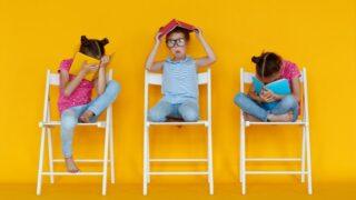 Lustige Kindermädchen lesen Bücher auf einem farbigen gelben Hintergrund