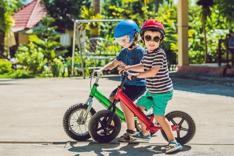 Zwei-kleine-Jungen-die-Spas-auf-dem-Laufrad-auf-einer-tropischen-Landstrase-haben.