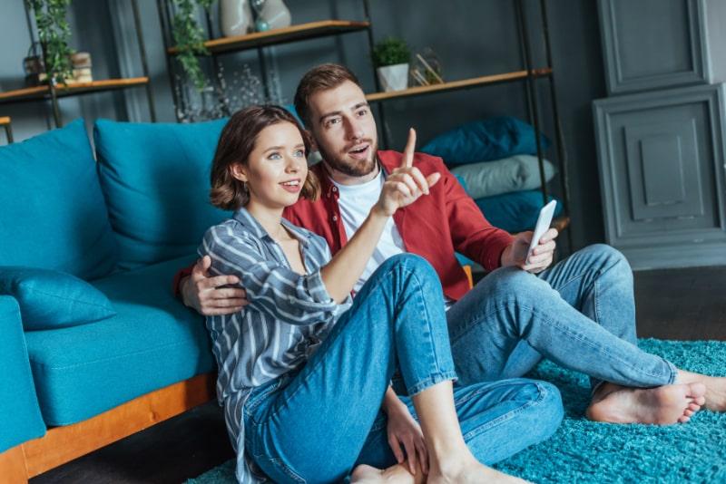 Attraktive-Frau-die-mit-dem-Finger-nahe-uberraschtem-Mann-zeigt-der-Smartphone-halt