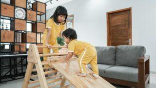 Das Baby klettert in Begleitung auf ein Pikler-Dreieck-Spielzeug