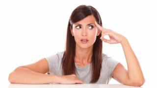 Erwachsene hispanische Frau, die sich fragt, während sie nach links schaut