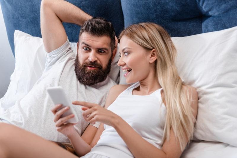 Frohliches-Madchen-das-mit-dem-Finger-auf-dem-Smartphone-Bildschirm-lachelt-und-zeigt-wahrend-ein-bartiger-uberraschter-Mann-die-Hand-auf-dem-Kopf-im-Bett-halt
