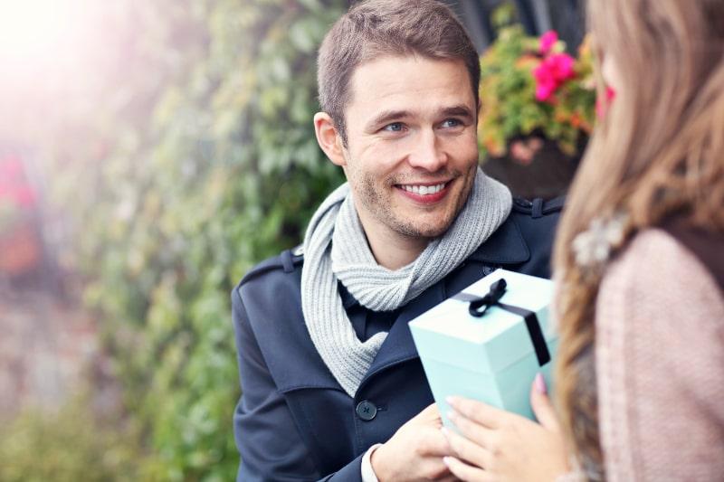 Junges-Paar-mit-Geschenk-im-Park