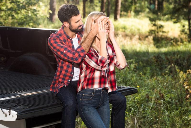 Lachelnder-Mann-der-die-Augen-der-Freundin-von-hinten-bedeckt-wahrend-er-im-Freien-auf-dem-Kofferraum-sitzt