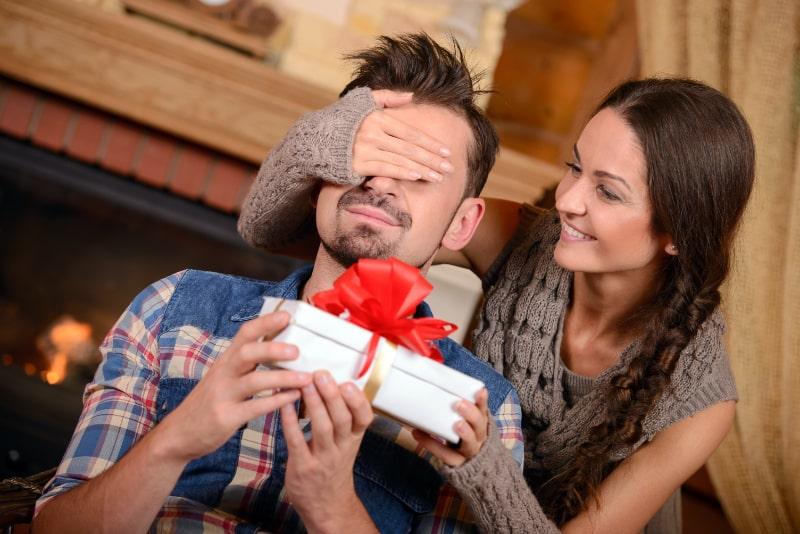 Mann-bekommt-ein-Geschenk-von-einer-Frau-in-der-Nahe-eines-Kamins