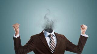 Überarbeiteter Burnout-Geschäftsmann, der kopflos vor Rauch steht