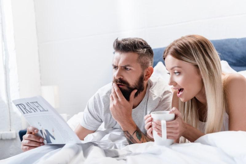 Uberraschter-Mann-und-junge-Frau-mit-Tasse-im-Bett-liegend-und-Reisezeitung-lesend
