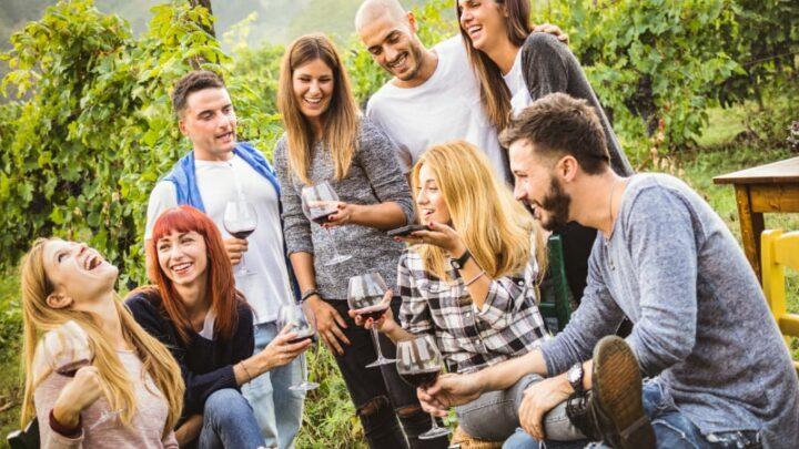 Fröhliche Freunde, die Spaß im Freien haben - Junge Leute, die zur Erntezeit Rotwein im Weingut des Bauernhauses trinken - Jugendfreundschaftskonzept mit Freunden