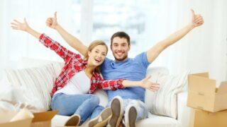 Lächelndes Paar, das sich auf dem Sofa im neuen Zuhause entspannt