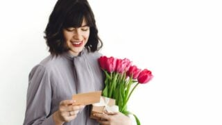 Schöne brünette Mädchen mit Blumenstrauß aus Tulpen, Geschenkbox und Grußkarte auf weißem Hintergrund drinnen, Platz für Text. Glückliche junge Frau mit Blumen. Schönen Muttertag.